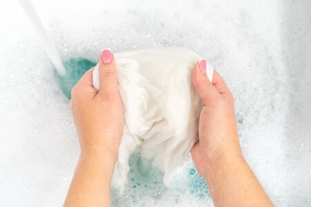 Hand washing white clothes in sink to bleach