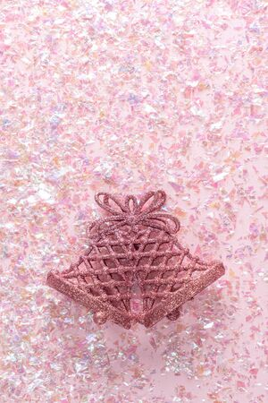 Two bells on pink background with tinsel. Minimal Christmas concept. Happy New Year. Flat lay, top view, copy space Stock Photo