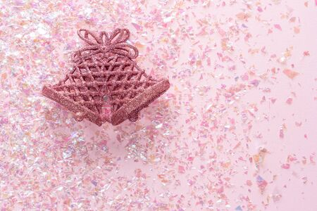 Vintage Jingle bell on pink glitter background. Minimal Christmas concept. Happy New Year. Flat lay, top view, copy space