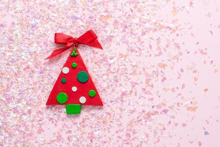 Vintage Plasticine clay Christmas tree on pink glitter background. Minimal Christmas concept. Happy New Year. Flat lay, top view, copy space