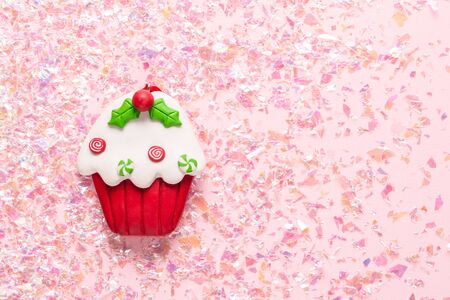 Vintage Plasticine clay cupcake on pink glitter background. Minimal Christmas concept. Happy New Year. Stock Photo