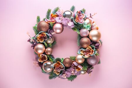 Beautiful unusual Christmas wreath decoration on pink background. flat lay
