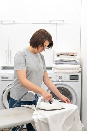 Woman ironing white shirt on board in laundry room with washing machine on background