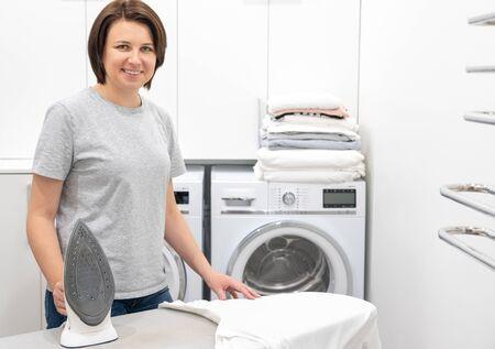 Mujer sonriendo mientras está de pie cerca de la tabla de planchar en el lavadero con lavadora en segundo plano. Foto de archivo