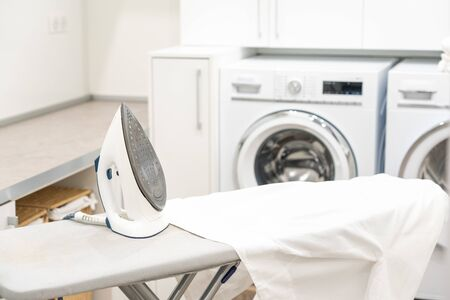 Ironing board with white shirt and iron in laundry room