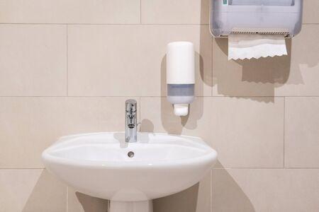 Waschbecken neben Seifenspenderpumpe und Papierhandtuchspender