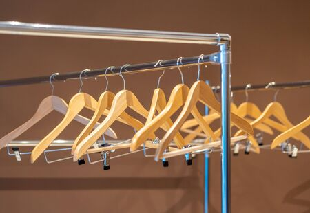 Wooden hangers on coat rack with no clothes in wardrobe Stock Photo