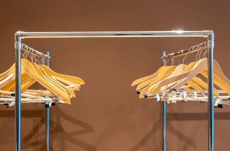Empty hangers on coat rack with no clothes in cloakroom Stock Photo