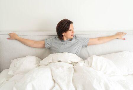 Lächelnde brünette Frau im Schlafanzug, die im Bett im Schlafzimmer sitzt