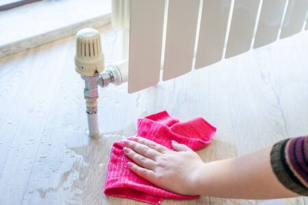Female hand with rag cleaning water from heating radiator leak Stock Photo