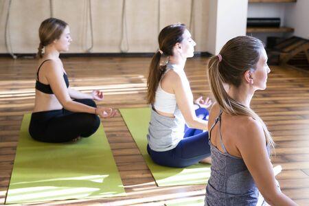 giovani donne nella lezione di yoga sedute e rilassate facendo meditazione posa del loto