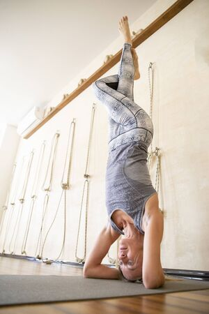 Young yoga woman standing on head during yoga class