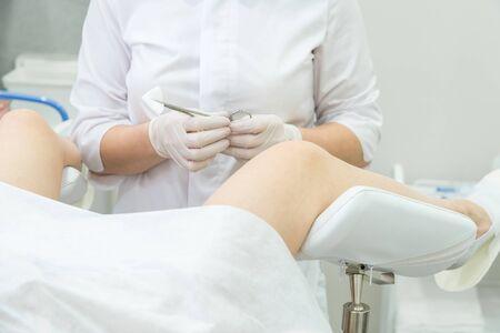 Ginecólogo profesional que examina a la paciente en silla ginecológica sosteniendo fórceps Foto de archivo