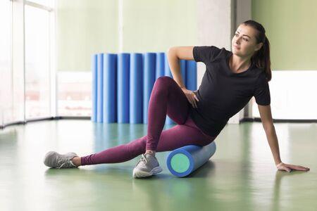 Attraktive Frau, die Schaumrollenübungen macht und in einem modernen hellen Fitnesscenter posiert
