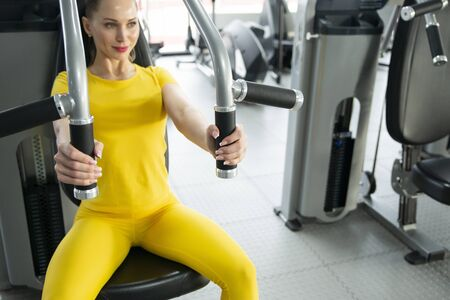 Torso portrait of Cheerful young adult caucasian woman working out on exercise machine inside gym Imagens