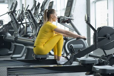 Side view of fit young women using rowing machine in health club Stock fotó