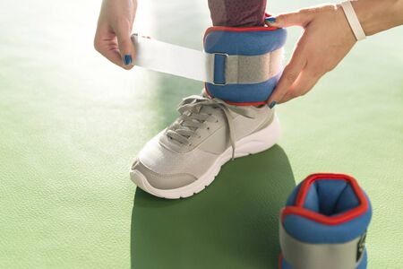 Woman putting on ankle wights before she starts a workout in a gym, health and fitness concept