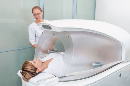 Modern spa treatment capsule in cosmetology clinic, cosmetologist operating equipment