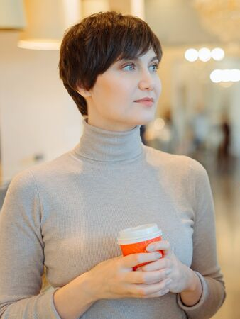 Young woman with short hair in cafe holding hot drink in paper cup