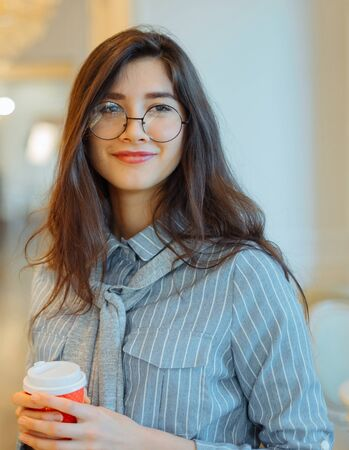 Young asian woman in cafe holding hot drink in paper cup