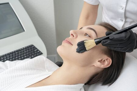 Cropped close up of a cosmetologist applying black mask on the face of a beautiful mature woman Stock Photo