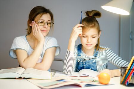 Mother and daughter doing homework together, styding and learning concept, doing tasks for school