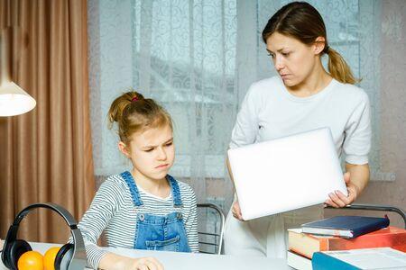 Madre discutiendo con su hija adolescente sobre la actividad en línea llevándose el portátil