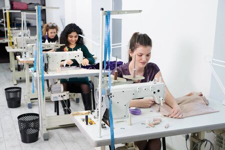 Junge Damenschneiderinnen nähen Kleidung an der Nähmaschine im Schneideratelier Standard-Bild