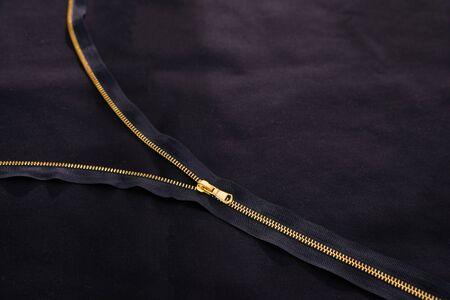 Offener goldener Reißverschluss auf schwarzem Stoff Standard-Bild