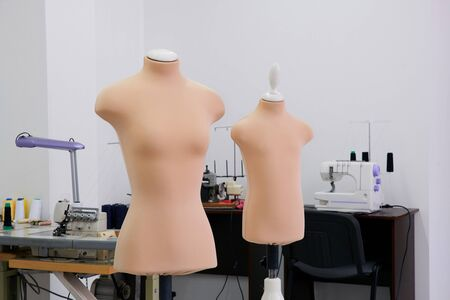 Mannequin dummy in a tailor shop with sewing machines on background, modern atelier studio