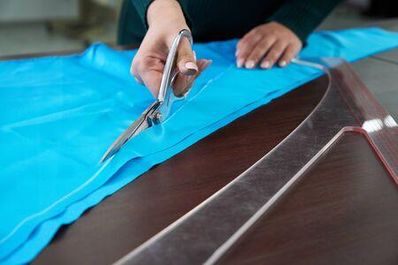 Dressmaker cutting fabric in atelier shop