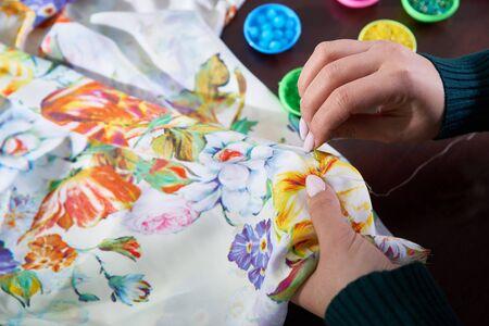 Nahaufnahme Hände der Frau Schneiderin (Schneiderin) Designer Hochzeitskleid näht Perlen zum Spitzen auf blauem Hintergrund im Studio