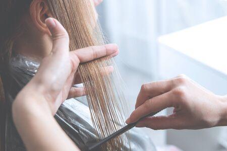 Hairdresser cut hair of a blonde young woman in hair salon, haze effect