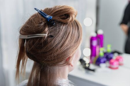 Young woman sitting in beauty hair salon style and waiting for hairdresser to make a hairdo