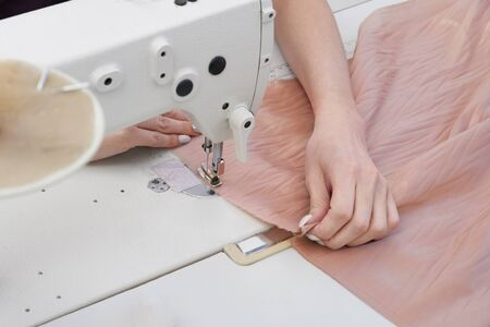 dressmaker using sewing machine in tailor studio, modern atelier shop
