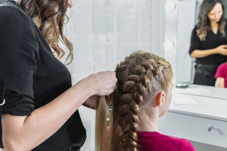 Hairdresser weaves a braid to a preteen blond girl Foto de archivo