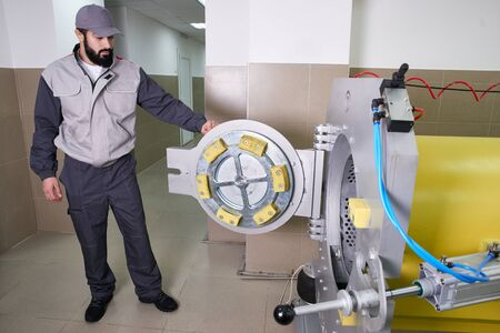 Men workers get carpet from an automatic washing machine and put in in dryer in the Laundry service