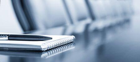 Blocco note su un tavolo con penna prima dell'incontro, tonalità blu, concetto di business con spazio di copia Archivio Fotografico