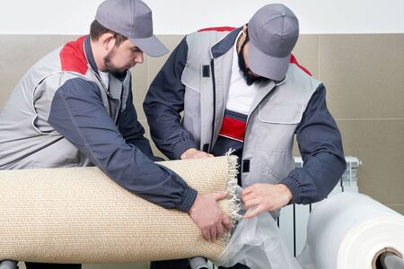 Men workers packing carpet in a plastic bag after cleaning it in automatic washing machine and dryer in the Laundry service Zdjęcie Seryjne