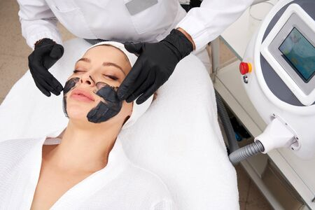 Cosmetologist applying black mask on the face of a beautiful woman for carbon peel Stock Photo