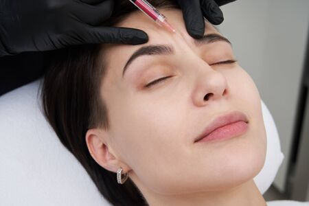 Beautiful woman gets an injection in her forehead Stock fotó