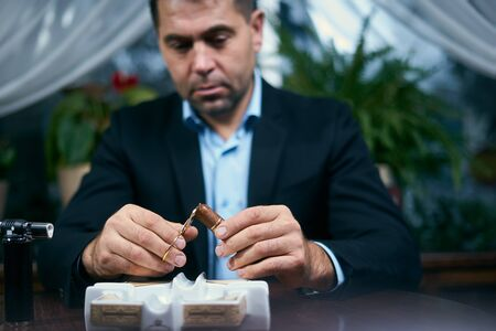 Man cutting cigar before smoking while sitting in a restaurant