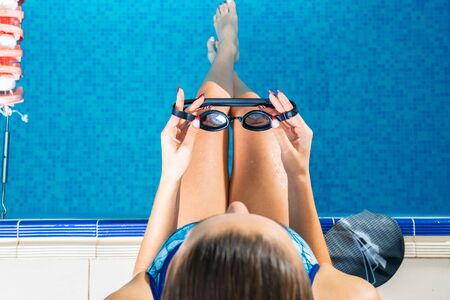 Young woman in swimming pool holding goggles getting ready to swim