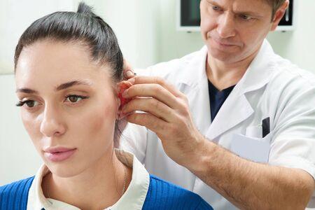 Plastic surgeon examines ear of patient before plastic surgery Standard-Bild