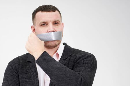 businessman is removing a piece of tape that has been covering his mouth