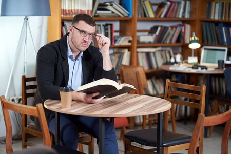 Man reading book and drinking coffee in a library cafe with many books on a background