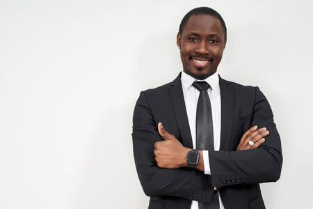 Smiling african businessman with thumbs up over grey background with copy space