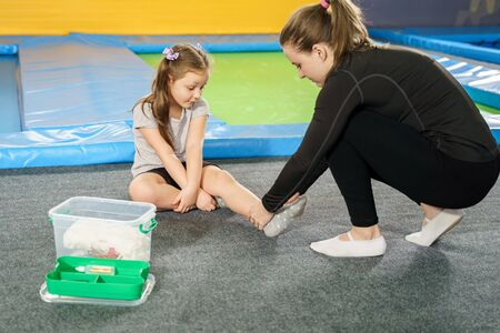 girl having pain in ankle and getting help after jumping on trampoline Banque d'images