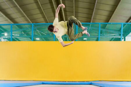 Teenage boy jumping on trampoline park in a sport center Stock Photo