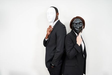 African man and Caucasian woman wearing black suits hiding face with plastic masks Stockfoto